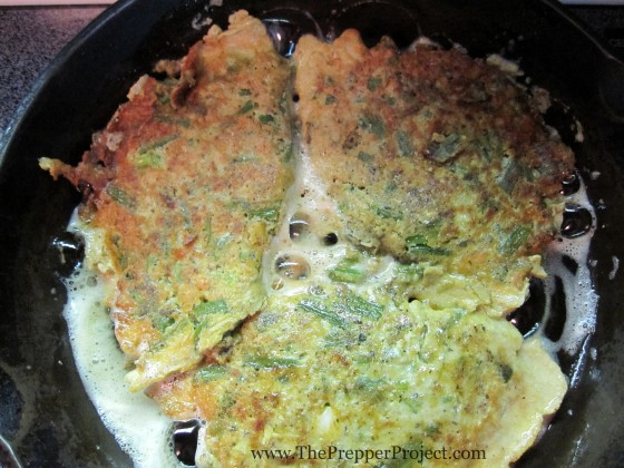 Frying up a pan of foraged burdock roots in egg batter.